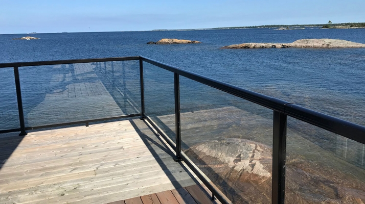 black-aluminum-railing-with-large-glass-panel-on-beautiful-deck